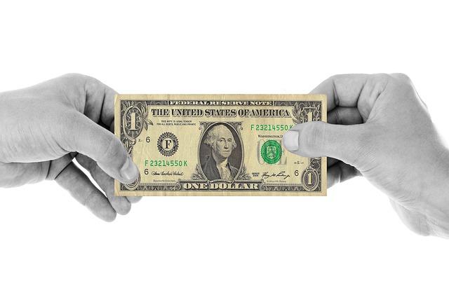 2 hands grabbing a dollar note